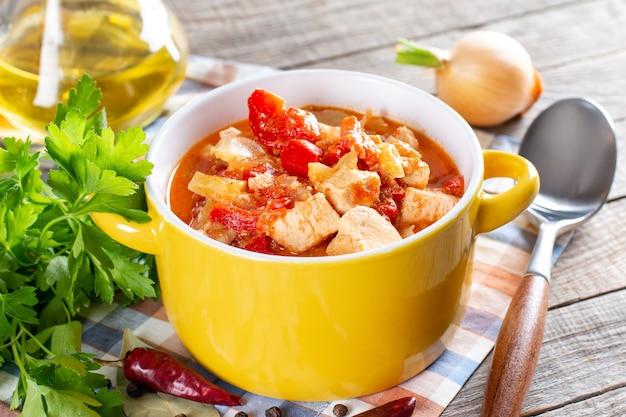 木製の背景のプレートにパプリカ、タマネギ、サワークリームとチキンシチュー。伝統的なハンガリー料理のパプリカッシュ。セレクティブフォーカス。