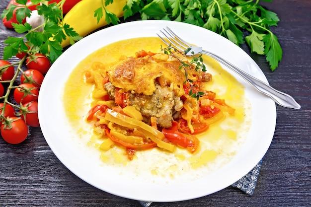 トマト、黄色と赤のピーマン、チーズをタオルに白いプレートで煮込んだチキン、タイム、パセリ、ニンニクを木の板の背景に