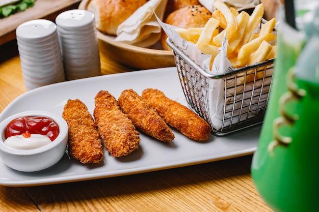 Il pollo attacca con la vista laterale del pepe del sale del ketchup della maionese delle patate fritte