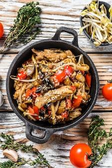 Chicken stir-fry in a pan.