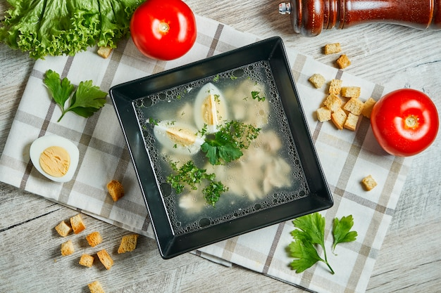 Chicken stock on a wooden table. light soup with egg, chicken meat in a composition with vegetables. top view
