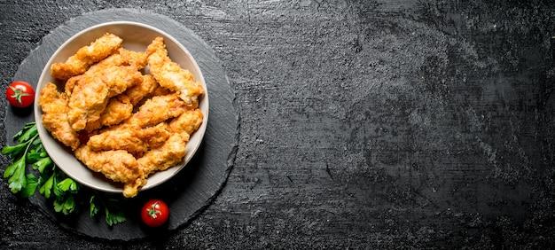 黒い素朴なテーブルの上にパセリとトマトとボウルのチキンストリップ