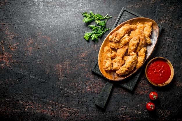暗い素朴なテーブルのボウルにパセリとトマトソースとまな板のチキンストリップ