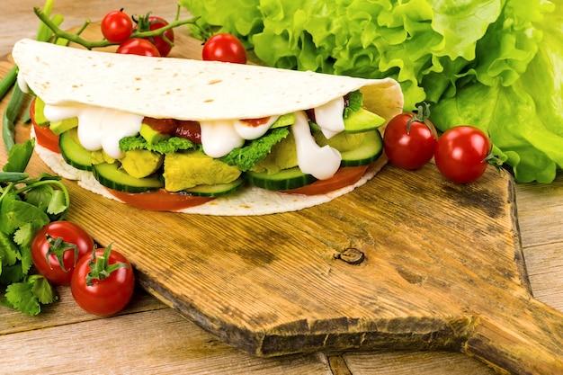鶏肉を詰めたシャワルマトルティーヤタコスは、古い素朴なまな板の上でドネルケバブサンドイッチジャイロファーストフードを野菜で包みます。セレクティブフォーカス。コピースペース