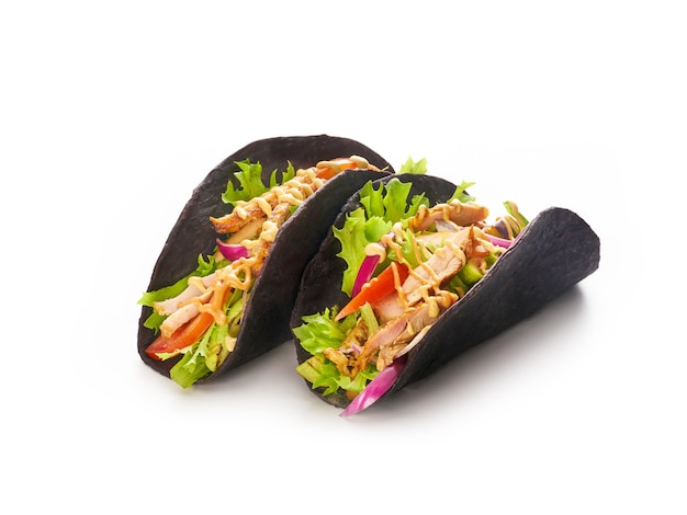 Chicken tacos with vegetables, red onion and bell peppers in black tortillas bread, mexican fast food concept