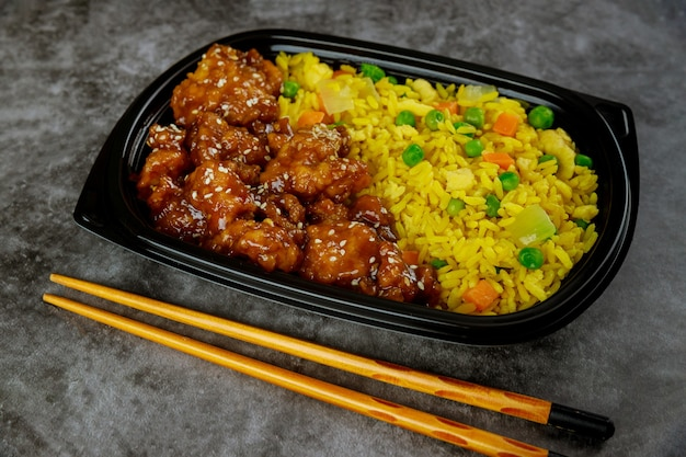 Chicken teriyaki in sweet and sour sauce with rice on plastic tray.