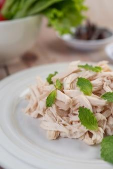 Il pollo bordato viene cotto e posto in un piatto bianco insieme a foglie di menta.