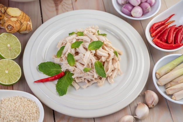 The chicken that is bordered is cooked and placed in a white plate along with mint leaves.