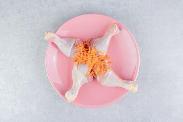 Куриное бедро и тертая морковь на тарелке, на мраморной поверхности