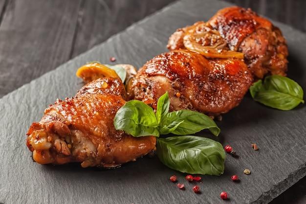 Куриные бедра и базилик на черном столе