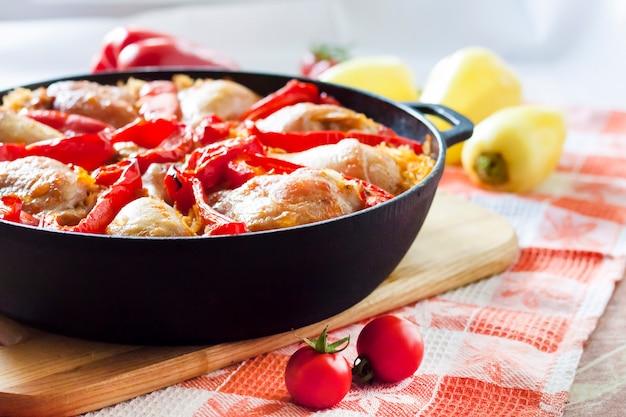 鋳鉄製の鍋でご飯と赤ピーマンのベッドの上で焼いた鶏もも肉と脚