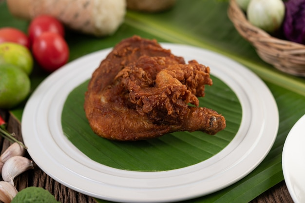 Chicken thighs fried on banana leaves on a white plate