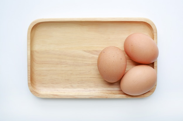 Chicken three eggs on wooden tray isolated on white background.