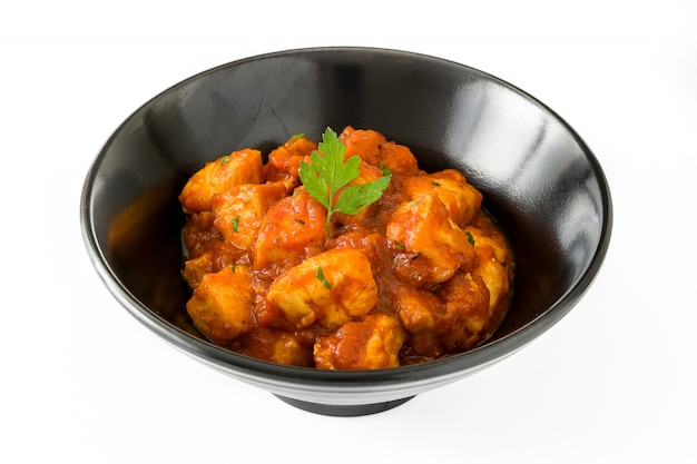 Chicken tikka masala in bowl on white