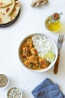 Куриный карри тикка масала с рисом, зеленью и перцем. индийская еда. национальная кухня.