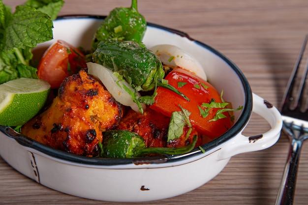 Курица тикка масала с острым мясом карри и курицей со свежими овощами Premium Фотографии