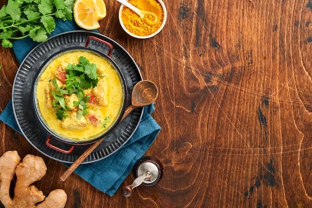 チキンティッカマサラ。暗い背景に伝統的なインド料理のカレーと食材。カレー、ライム、生姜、コリアンダー、チリ、ライス、ハーブ、スパイス。コピースペースのある上面図。