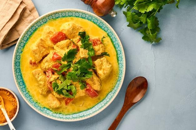 Куриный тикка масала. традиционное карри индийской кухни и ингредиенты на темном фоне. карри, лайм, имбирь, кинза, перец чили, рис, зелень и специи. вид сверху с копией пространства.