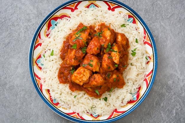 Chicken tikka masala with basmati rice on gray