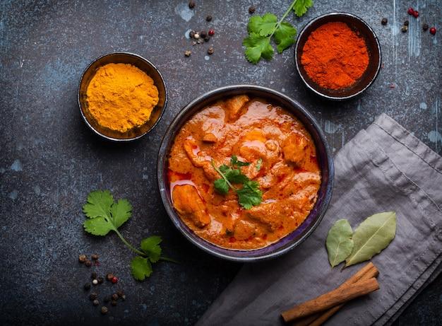 素朴なセラミックボウル、人気のインド料理、コンクリートの背景、上面図で提供されるスパイシーなカレー肉とチキンティッカマサラ