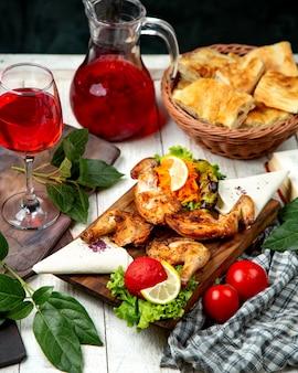 Tabacco di pollo su una tavola di legno e un bicchiere di composta