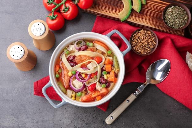 キッチンテーブルに野菜とチキントルティーヤスープ