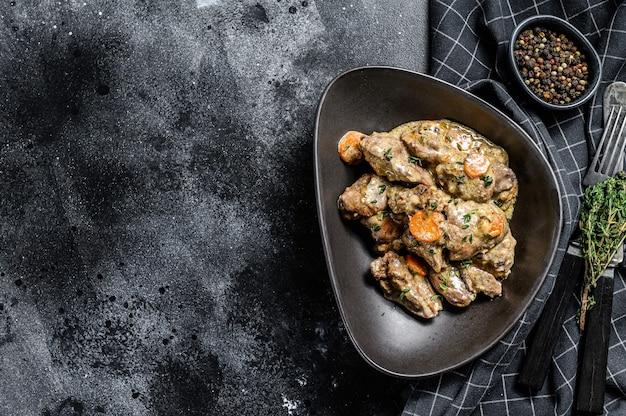 Тушеная курица, печень индейки с луком в тарелке. черный фон. вид сверху. скопируйте пространство.