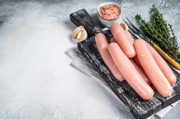 Chicken and turkey meat raw sausages on a wooden board with thyme