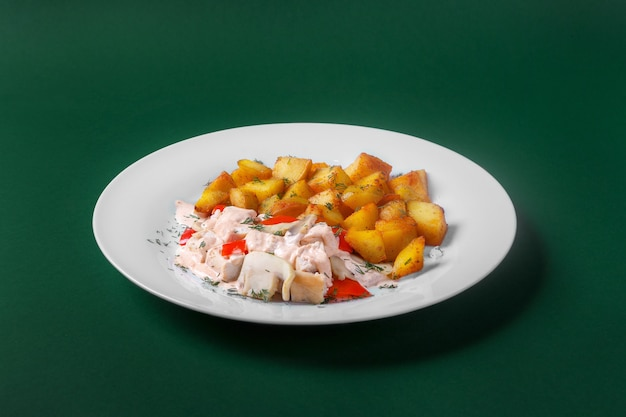 Chicken, turkey with cream sauce and red pepper, fried potatoes. on a white plate. green background. side view