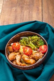 블루 냅킨에 코코넛 껍질 접시에 일본 소스에 치킨 우동. 세로 사진