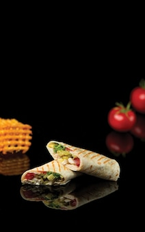Chicken vegetable lavash shaurma cut into two pieces.