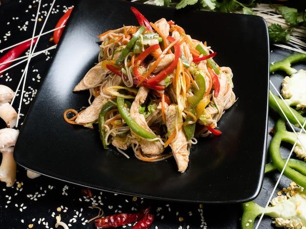Салат с курицей и овощами на тарелке