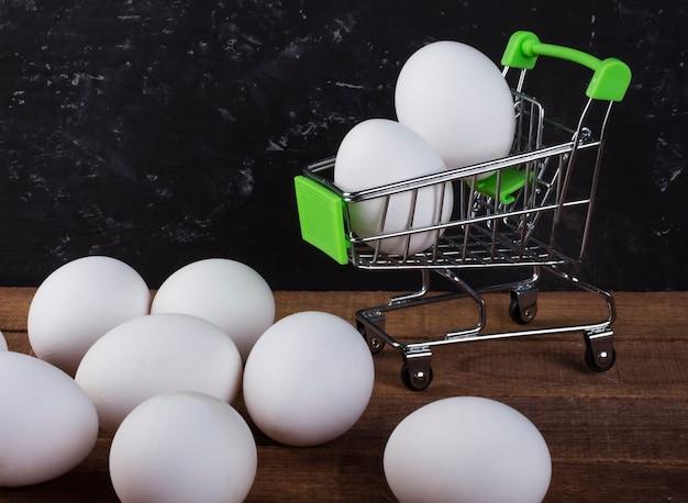 テーブルとスペースのコピーと黒の背景の買い物かごに鶏の白い卵。