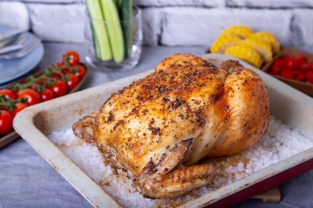Цыпленок весь запеченный на соли. с кукурузой в початках, помидорами черри, огурцами и перцем халапеньо. выборочный фокус, крупный план.