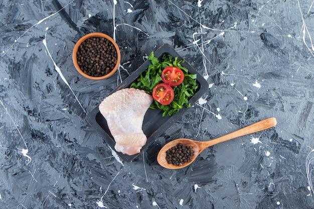 Куриное крылышко и овощ на доске рядом с миской и ложкой для специй, на мраморном фоне.
