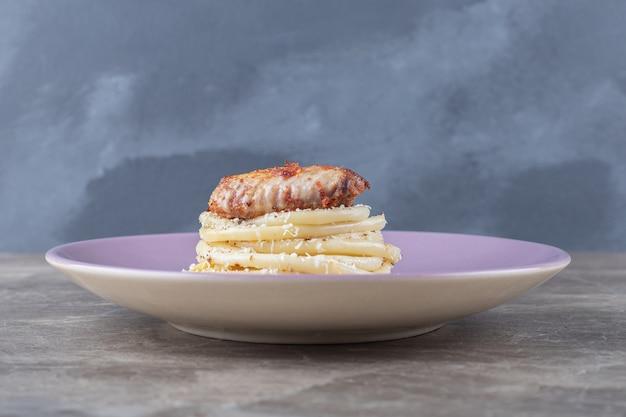Куриное крылышко над спагетти на тарелке, на мраморе.