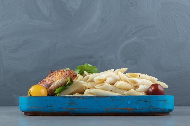 Ala di pollo con pasta di penne sul piatto blu.