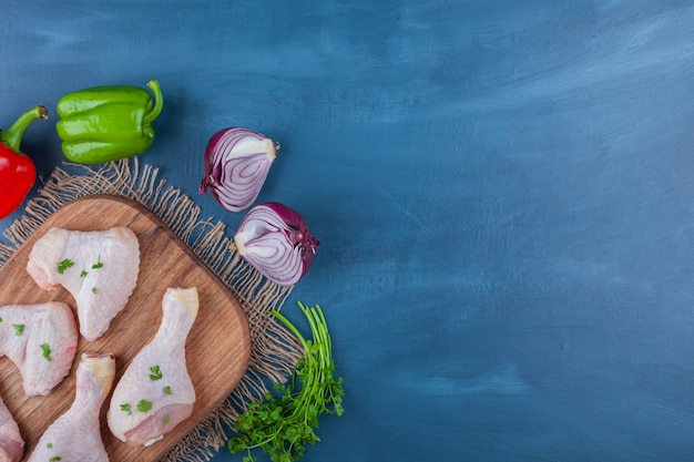 Куриные крылышки и голени на разделочной доске рядом с овощами, на синем фоне.