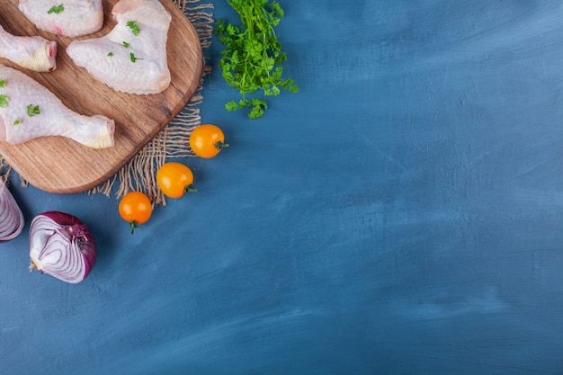 Куриные крылышки и голени на разделочной доске рядом с овощами, на синем.