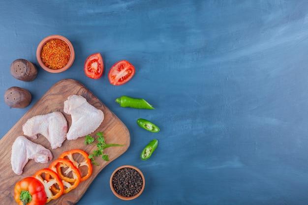 Куриные крылышки и нарезанные овощи на разделочной доске, на синем фоне.