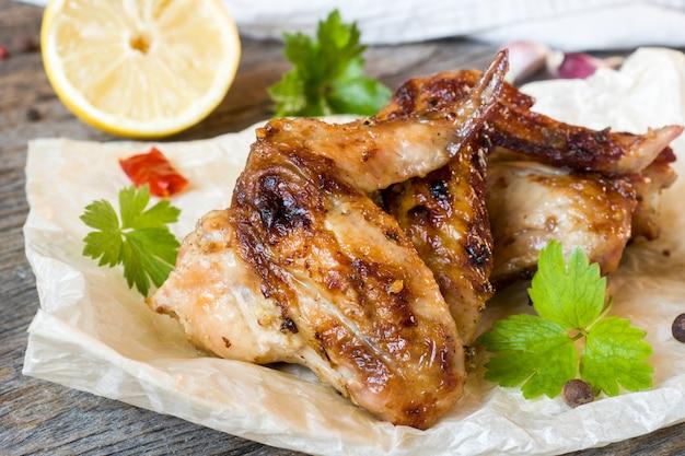 나무 테이블에 레몬, 신선한 허브와 그릴에 구운 닭 날개.