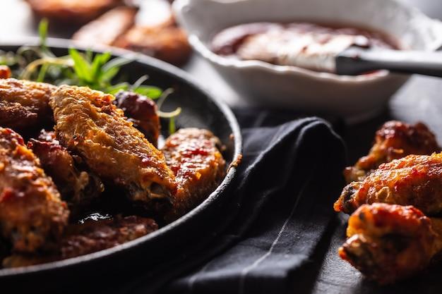 手羽先のバーベキュー、鋳鉄製のベーキングディッシュ、バーベキューソースとローズマリー。