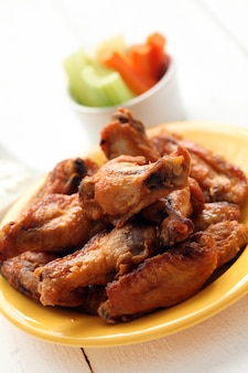 Chicken wings in bowl with vegetables