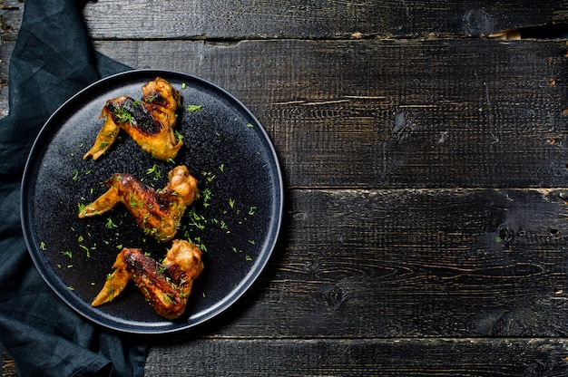 Chicken wings grilled in honey marinade on a black plate.
