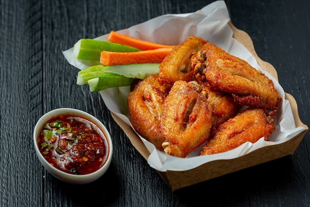 Chicken wings in paper box on a black