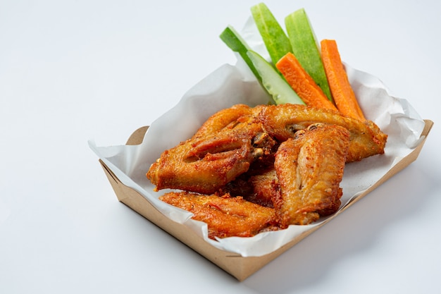 Chicken wings in paper box on a white