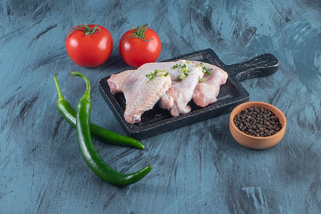 Chicken wings and vegetables on a board , on the blue surface.