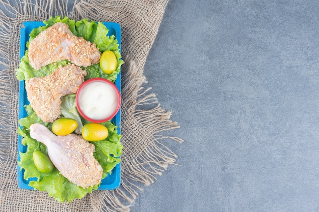 Ali di pollo con pangrattato e verdure sulla zolla blu.