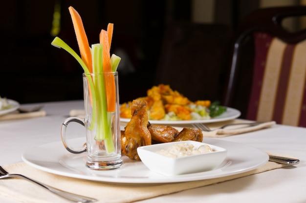 にんじんとセロリの手羽先とレストランのテーブルのディップ
