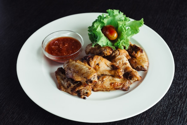 Chicken wings with sauce on plate on wooden table